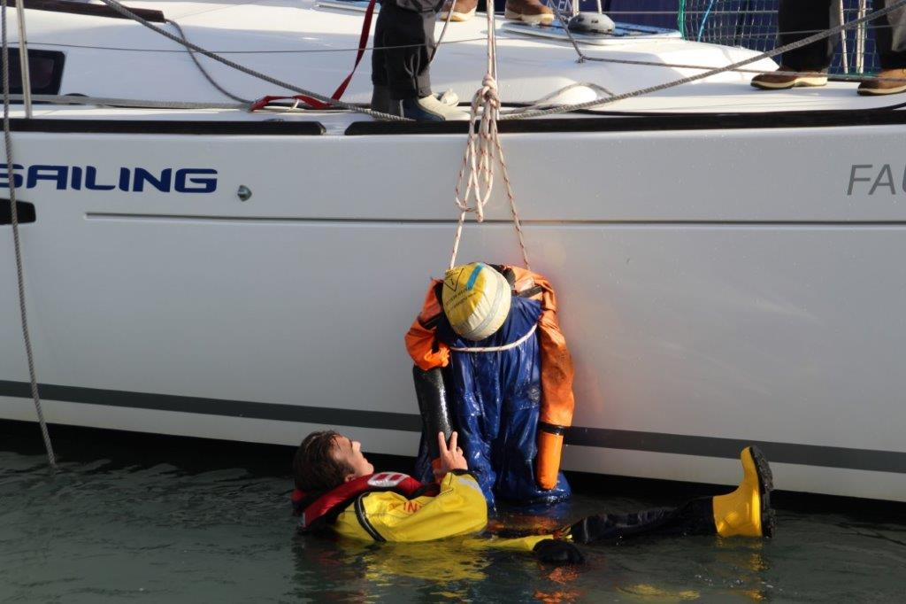 MOB rescue dummy being lifted onboard a yacht