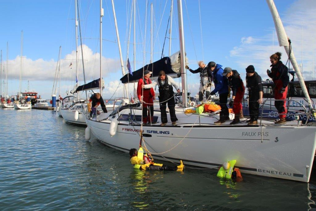 Lady in the water being rescued back onto a yacht