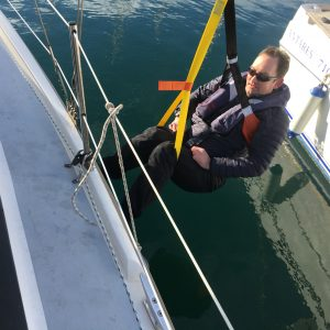 picture showing Andy Burton being recovered from the water using two helicopter strops and the main halyard