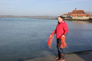 Picture of Andy Burton holding the TREM Survivor strop after using it - the rope is gathered up into two loops and one is held in each hand. In the background there is sea and shoreline and houses.