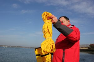 Picture of Andy Burton holding the rope from a Jimmy Green Oscar Recovery System with sea and sky in the background.