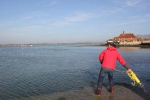 Picture of Andy Burton throwing the Plastimo Rescue Line with sea and shoreline and houses in the background