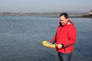 Picture of Andy Burton holding the Plastimo Rescue line before throwing it with sea and shoreline in the background.