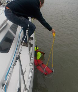 Picture of a sailor guiding a chain recovery strop under the knees of a KIM Fibrelight Rescue Dummy