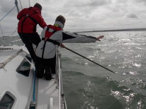 Sailor pointing to the Man Overbaord and giving directions to the helmsman